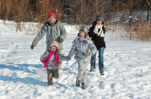 Happy family in winter, having fun with snow outdoors on weekend