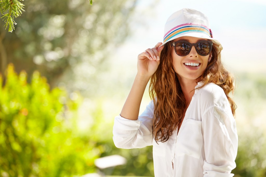 Smiling summer woman with hat and sunglasses protecting her skin from sun damage