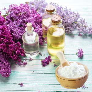 Essential aroma oil with lilac on turquoise painted wooden background, with corn starch for dry shampoo recipe