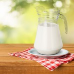 Jug of milk on red and white napkin on wood table
