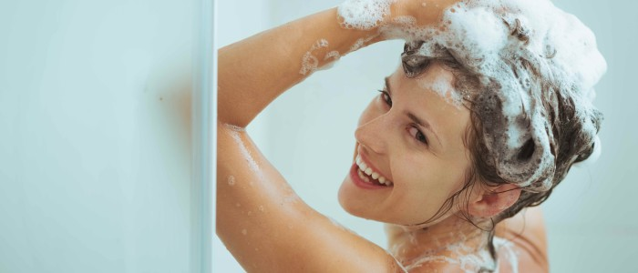 Smiling young woman washing head with shampoo - Blog Photo