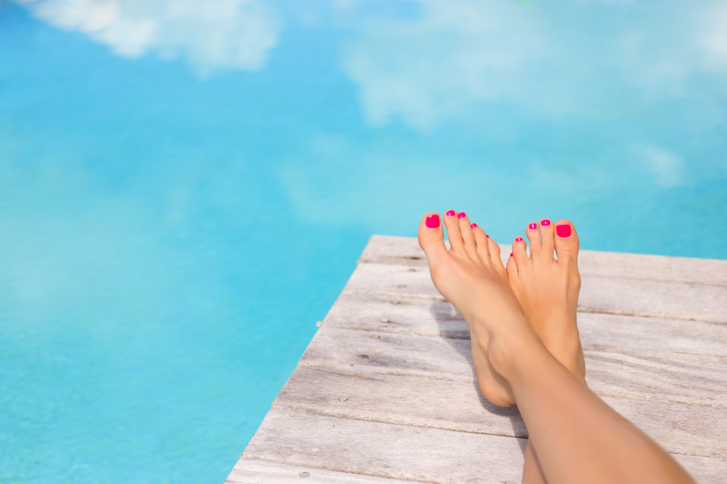 woman with red toes on dock by water