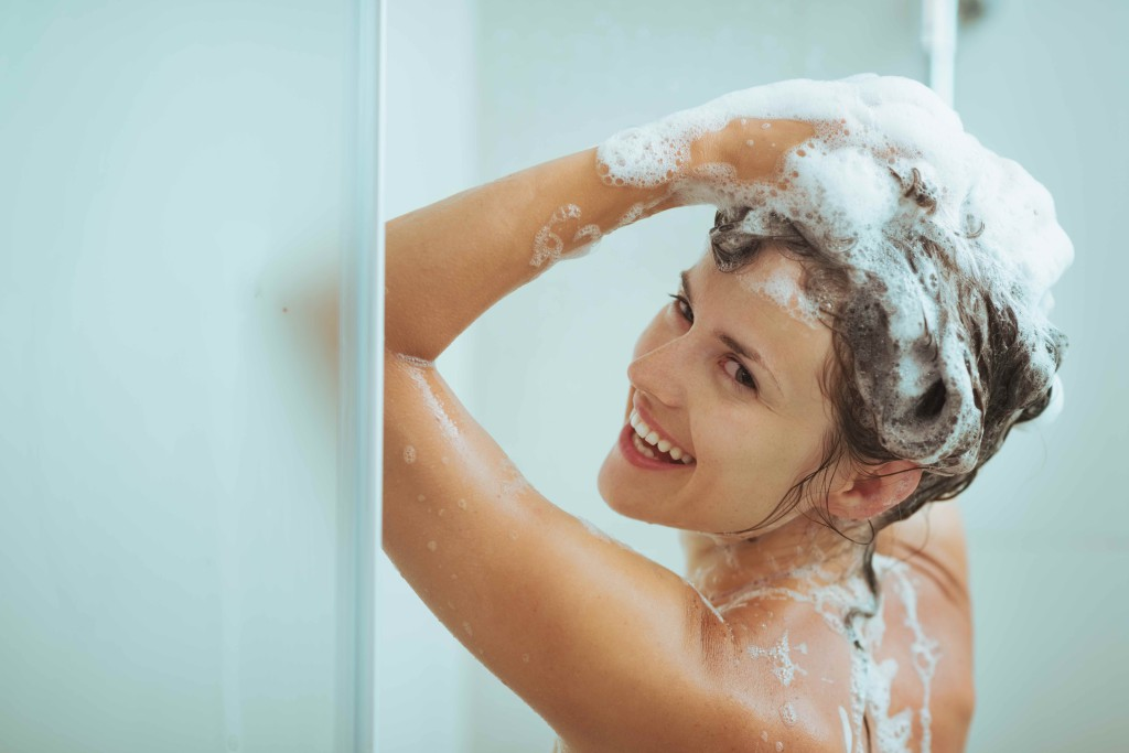 Smiling young woman washing head with shampoo. How to wash your hair