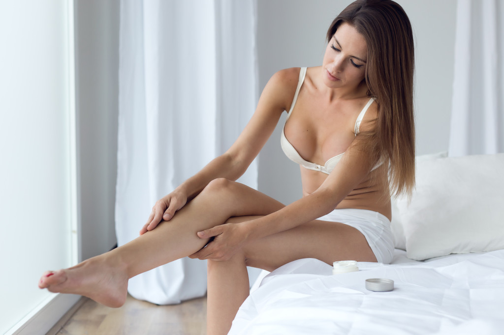 woman applying body cream on legs.