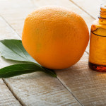 Orange Peel oil with orange on wooden background. Selective focus.