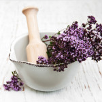 thyme flowers in a mortar on a old wooden background