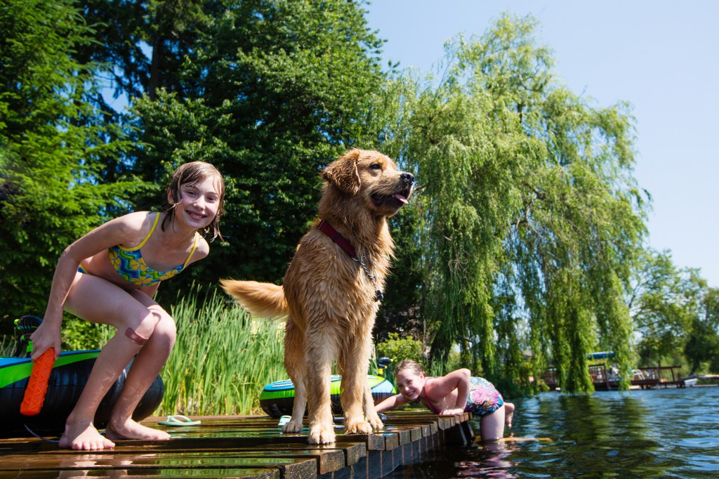 Two young girls playing with their happy dog on a lake.