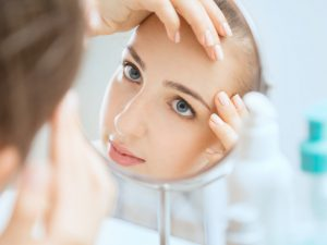 Shot of a reflection of a young woman examining her face in the