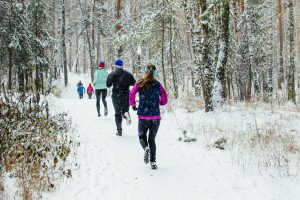group of runners running in winter forest